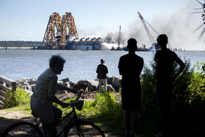 Residents watch firefighters hose down the hull of the overturned cargo ship Golden Ray, Friday, May 14, 2021, in Brunswick, Ga. The Golden Ray had roughly 4,200 vehicles in its cargo decks when it capsized off St. Simons Island south of Savannah, on Sept. 8, 2019. (AP Photo/Stephen B. Morton)