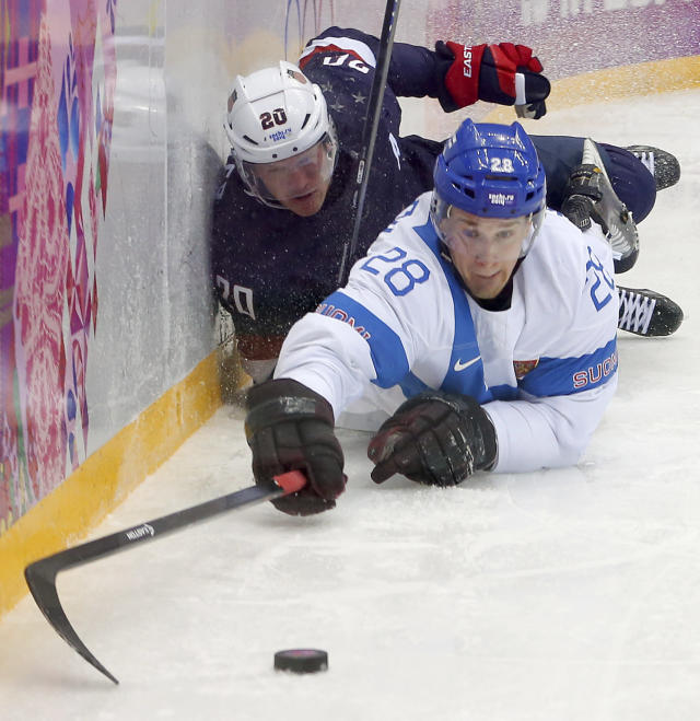 USA forward Blake Wheeler and USA defenseman dive for the puck during the third period of the men's bronze medal ice hockey game at the 2014 Winter Olympics, Saturday, Feb. 22, 2014, in Sochi, Russia. (AP Photo/Petr David Josek)