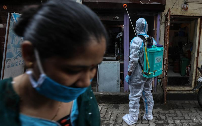 An Indian civic worker sprays disinfectant in the residential area of a 'containment zone' in Malvani, a Covid-19 hotspot, in Mumbai, India - Shutterstock