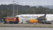 An airport fire engine passes by a Thomas Cook aircraft on the ground at Gatwick Airport, England, Monday, Sept. 23, 2019. British tour company Thomas Cook collapsed early Monday after failing to secure emergency funding, leaving tens of thousands of vacationers stranded abroad. (AP Photo/Alastair Grant)