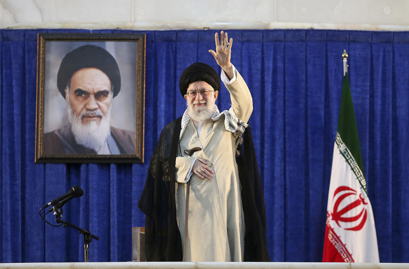 In this picture released by the official website of the office of the Iranian supreme leader, Supreme Leader Ayatollah Ali Khamenei waves to the crowd while attending a ceremony marking 30th death anniversary of the late revolutionary founder Ayatollah Khomeini, shown in the poster at rear, at his mausoleum just outside Tehran, Iran, Tuesday, June 4, 2019. Ayatollah Khamenei said his country will continue resisting U.S. economic and political pressure on his country. (Office of the Iranian Supreme Leader via AP)