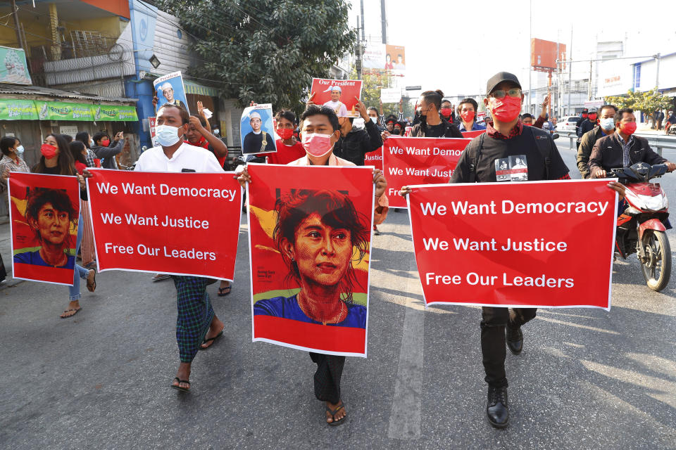 Protesters holding an image of deposed leader Aung San Suu Kyi & President Win Myint in Mandalay, Myanmar on Monday, Feb. 8, 2021. A protest against Myanmar's one-week-old military government swelled rapidly Monday morning as opposition to the coup grew increasingly bold. (AP Photo)