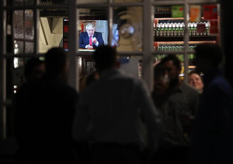 Customers at the Westminster Arms pub in London watch Prime Minister Boris Johnson address the nation regarding new coronavirus restrictions, including office staff working from home, the wider use of face masks and a 10pm curfew on pubs and restaurants.