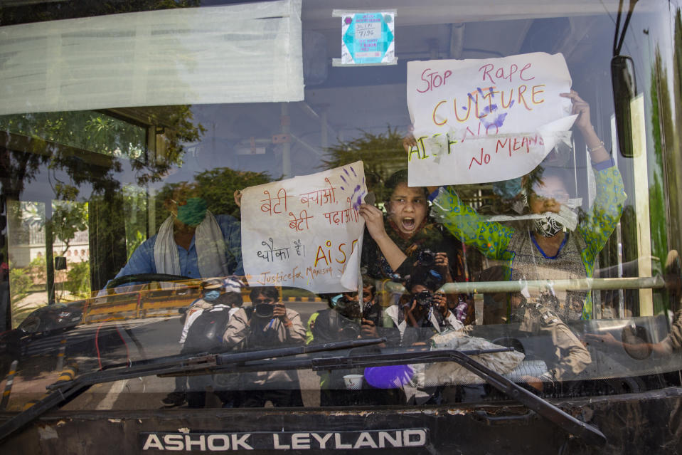 Indian activists hold placards and shout slogans from inside a bus after being detained during a protest in New Delhi, India, Wednesday, Sept. 30, 2020. The gang rape and killing of the woman from the lowest rung of India's caste system has sparked outrage across the country with several politicians and activists demanding justice and protesters rallying on the streets. (AP Photo/Altaf Qadri)