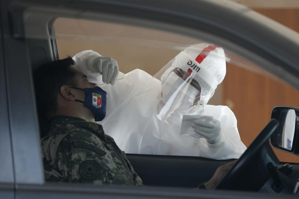 A nurse takes a sample from an army officer for a COVID-19 test at a Public Health Ministry post where drivers wait their turn in a line of cars in Asuncion, Paraguay, Tuesday, Aug. 11, 2020. (AP Photo/Jorge Saenz)