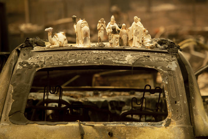 <p>Figurines scorched by the Camp Fire rest sit atop a car on Pearson Road, Monday in Paradise, Calif. (Photo: Noah Berger/AP) </p>
