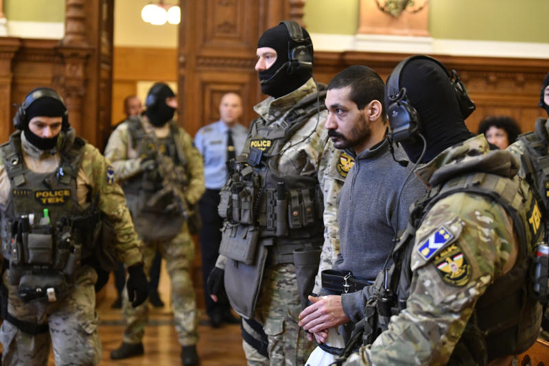 A Syrian man identified as Hassan F., second right, is escorted by Police officers as he arrives at the Metropolitan Court in Budapest, Hungary, Wednesday, Nov. 13, 2019. Prosecutors said the 27-year-old man identified only as Hassan F. participated in the beheading of a religious leader in the city of al-Sukhnah in Homs province and was also involved in the killings of at least 25 people. (Zsolt Szigetvary/MTI via AP)