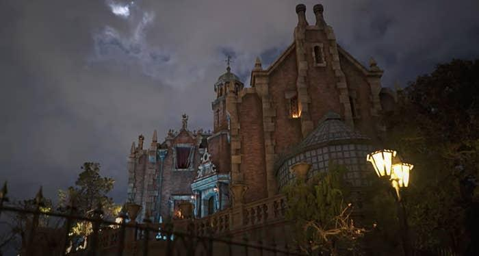 Exterior of the Haunted Mansion in Tokyo Disneyland, which features a brick building and a small greenhouse