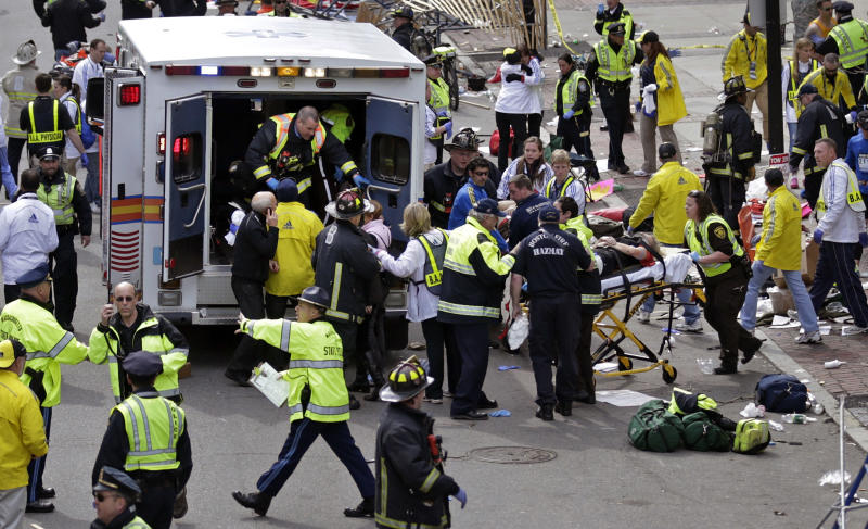 FILE - In this April 15, 2013 file photo, medical workers aid injured people after two bombs exploded near the finish line of the Boston Marathon in Boston. While giving is the reliable flip side to tragic events, charity watchdog groups recommend seeking out well-established charities, or credibly backed efforts like The One Fund, established by Massachusetts Gov. Deval Patrick and Boston Mayor Thomas Menino. (AP Photo/Charles Krupa, File)