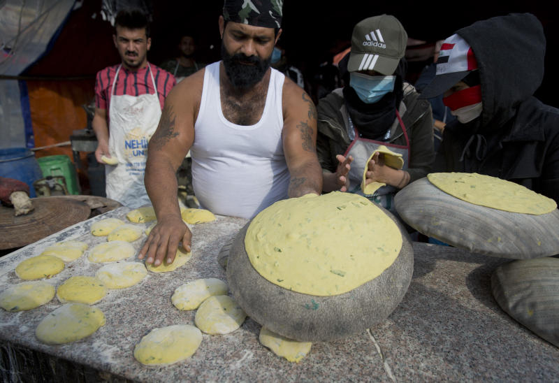 In this photo taken Monday, Dec. 9, 2019, a volunteer chef serves free portions of the popular Arouk bread, wheat flour mixed with meat and onions, to protester in the center of Baghdad, Iraq. In Baghdad's Tahrir Square, there are the anti-government protesters demonstrating for a better future for Iraq, and there are the volunteers who feed them. From stuffed lamb and fish, to the giant pots of soups and rice to the plates of lentils and beans, there is no shortage of food to go around. Volunteers from the capital and southern provinces cook traditional dishes that reflect the country's rich cuisine and bring protesters together.  (AP Photo/Nasser Nasser)