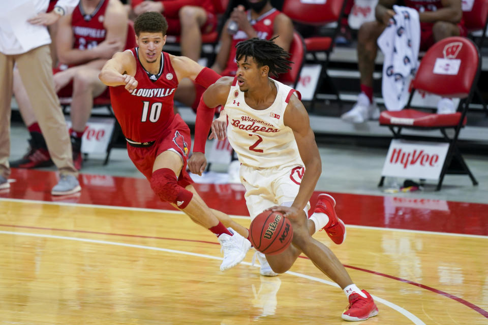 Wisconsin's Aleem Ford (2) drives against Louisville's Samuell Williamson (10) during the first half of an NCAA college basketball game Saturday, Dec. 19, 2020, in Madison, Wis. (AP Photo/Andy Manis)