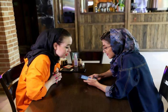 """Atefeh Khani and her friend check the """"Hamdam"""" dating app on her phone in a cafe in Tehran"""