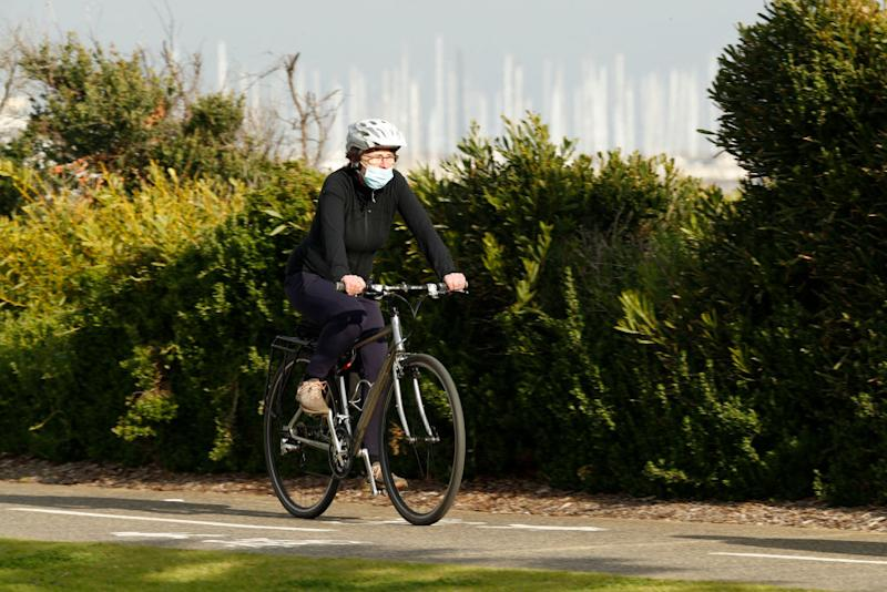 A woman, wearing a face mask, cycles along St Kilda.