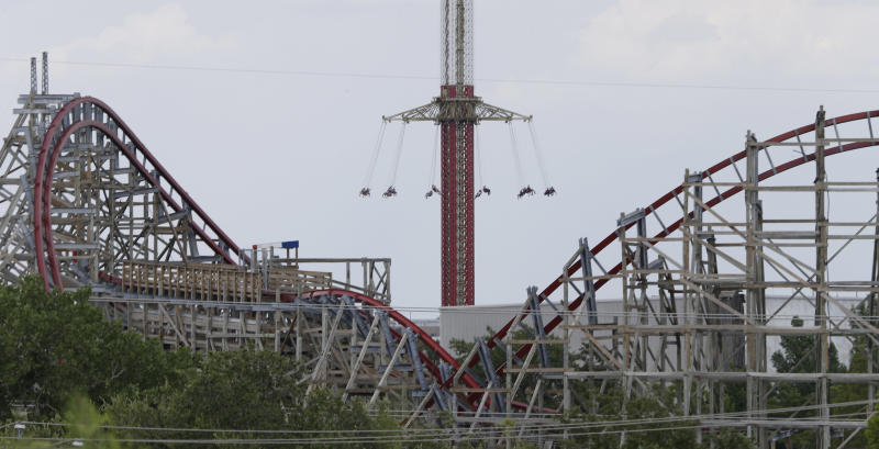 The Texas Giant roller coaster ride sits idle in the foreground as people take in another ride a the Six Flags Over Texas park Saturday, July 20, 2013, in Arlington, Texas. Investigators will try to determine if a woman who died while riding the roller coaster at the amusement park Friday night fell from the ride after some witnesses said she wasn't properly secured.(AP Photo/LM Otero )