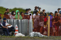 People watch from behind a security fence during the final day of the surfing competition at the 2020 Summer Olympics, Tuesday, July 27, 2021, at Tsurigasaki beach in Ichinomiya, Japan. The Olympic beach party that never was may be the only sore spot for surfing's long-awaited debut that finished triumphantly this week. Some local Japanese fans and beachgoers did manage to find a way to lay eyes on the athletes and the competition site once the games began. (AP Photo/Francisco Seco)