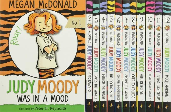 A stack of Judy Moody books, featuring one with her on the cover, a girl with short red hair and her arms crossed, wearing tiger print pants. Book title reads: Judy Moody Was In A Mood