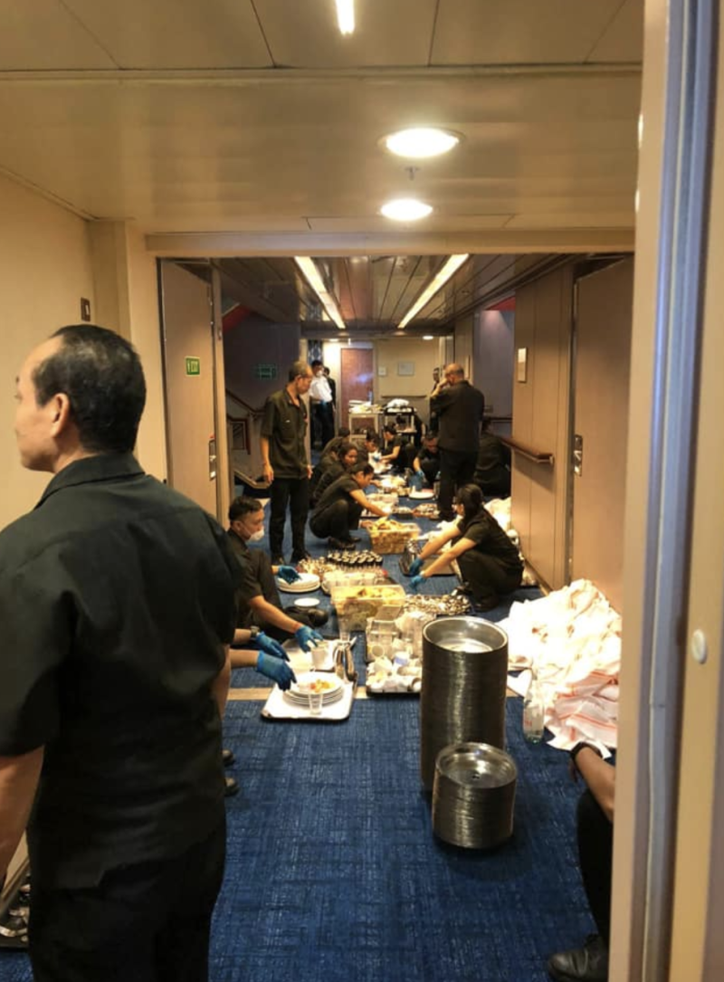 Cruise crew members are seen stacking dirty dishes in the cruise's hall. Source: Facebook