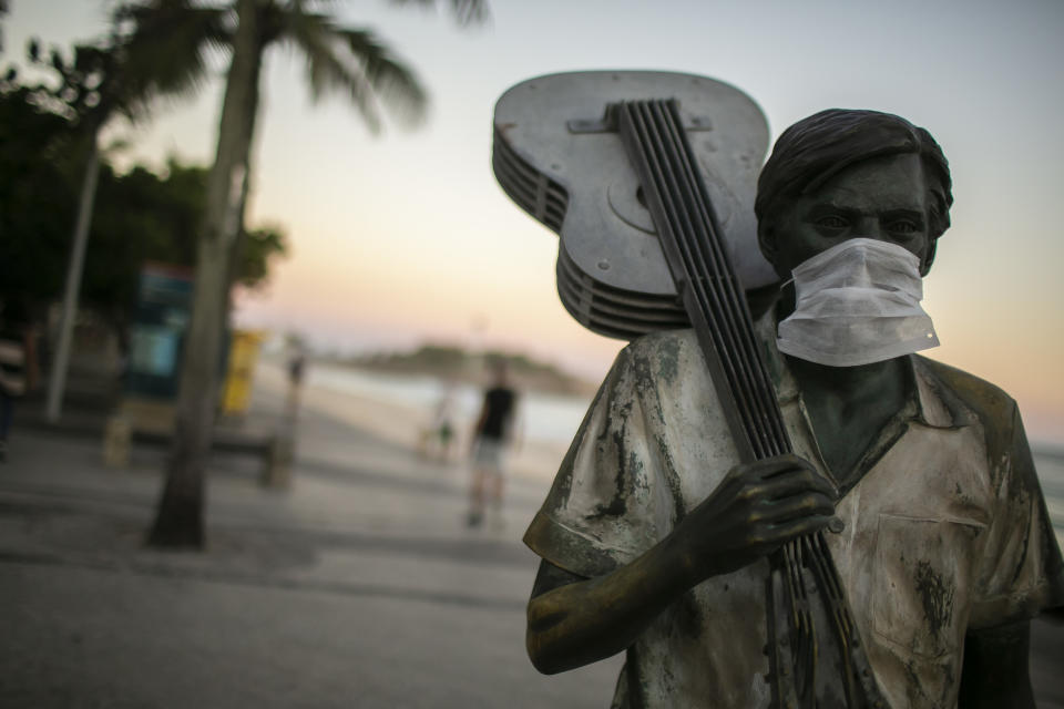 """RIO DE JANEIRO, BRAZIL - APRIL 24: Statue of a Brazilian musician and composer Antonio Carlos """"Tom"""" Jobim wearing a mask on Arpoador beach on April 24, 2020 in Rio de Janeiro, Brazil. Rio de Janeiro statues dawned wearing masks to draw attention of the population to the decree of Mayor Marcelo Crivella, which makes the use of the accessory mandatory across the city. According to the Brazilian Health Ministry, Brazil has 52.995 positive cases of coronavirus (COVID-19) and a total of 3.670 deaths. (Photo by Bruna Prado/Getty Images)"""
