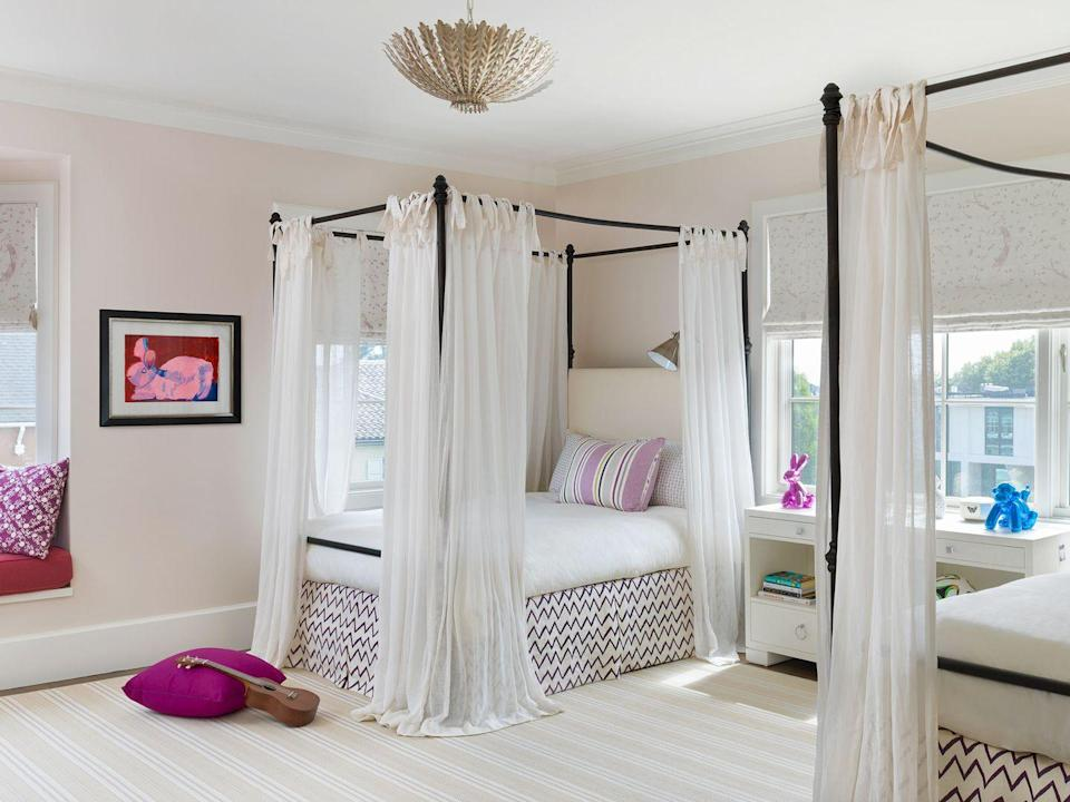 """<p>What teenager doesn't love privacy? Give them a little extra with curtains around a four-poster bed. Not only will it allow for those weekend morning sleep-ins, but it also introduces some polished style. In this bedroom by <a href=""""https://heatherhilliard.com/"""" rel=""""nofollow noopener"""" target=""""_blank"""" data-ylk=""""slk:Heather Hilliard Design"""" class=""""link rapid-noclick-resp"""">Heather Hilliard Design</a>, the zigzag bed skirt and striped pillow add just enough color to keep things youthful. </p>"""