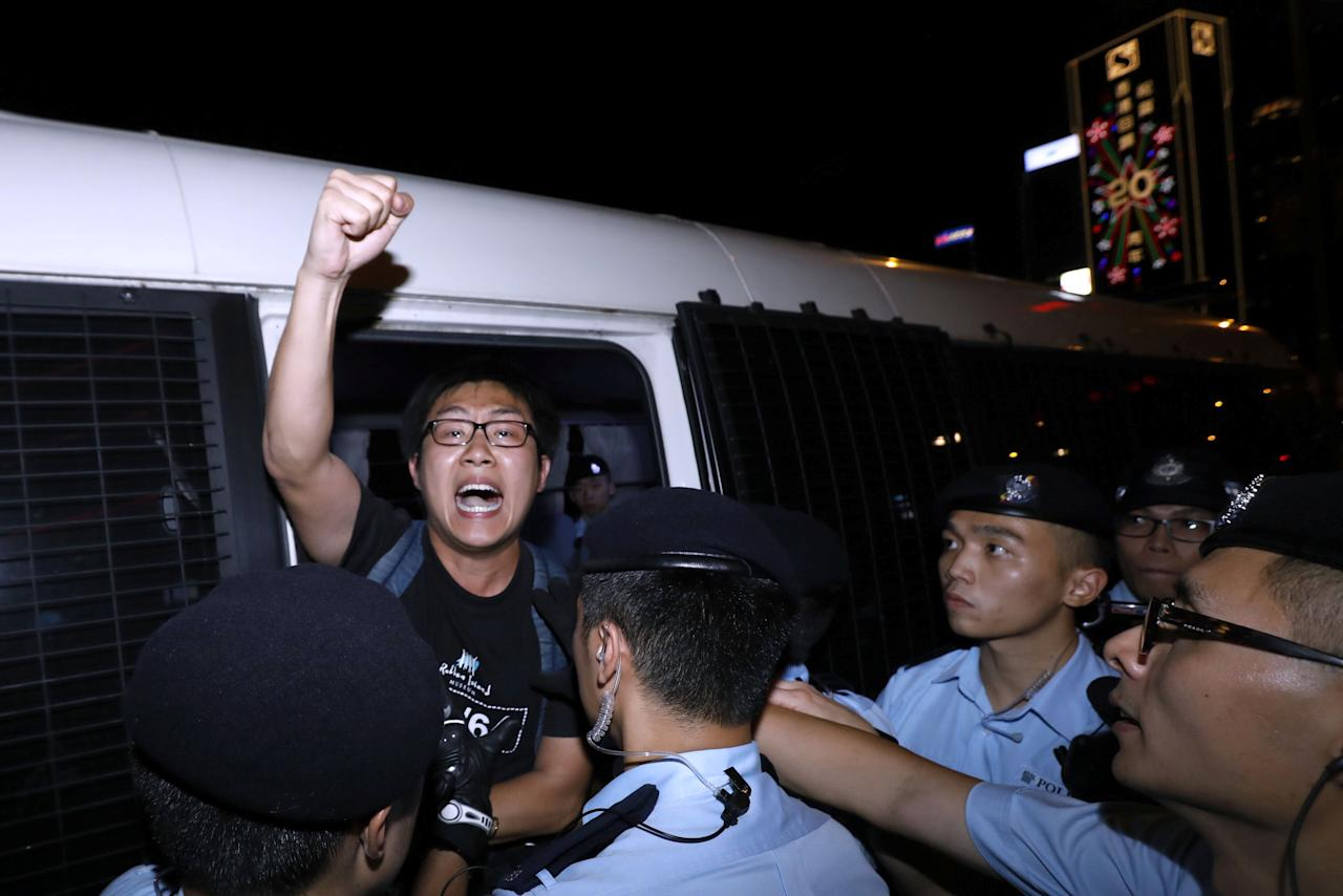 Pro-democracy activist Raphael Wong shouts as he is carried by policemen as protesters are arrested at a monument symbolising the city's handover from British to Chinese rule, a day before Chinese President Xi Jinping is due to arrive for the celebrations, in Hong Kong, China June 28, 2017. REUTERS/Tyrone Siu