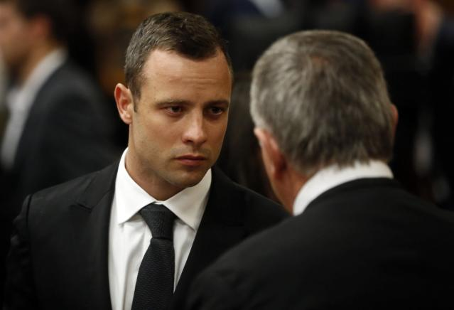 Olympic and Paralympic track star Oscar Pistorius confers with his lawyer Barry Roux on the third day of his trial for the murder of his girlfriend Reeva Steenkamp at the North Gauteng High Court in Pretoria, March 5, 2014. REUTERS/Mike Hutchings (SOUTH AFRICA - Tags: SPORT CRIME LAW ATHLETICS)
