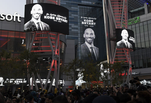 Electronic signs honor Kobe Bryant at L.A. Live in Los Angeles on Sunday, Jan. 26, 2020, following reports of his death in a helicopter crash in southern California. (AP Photo/Michael Owen Baker)