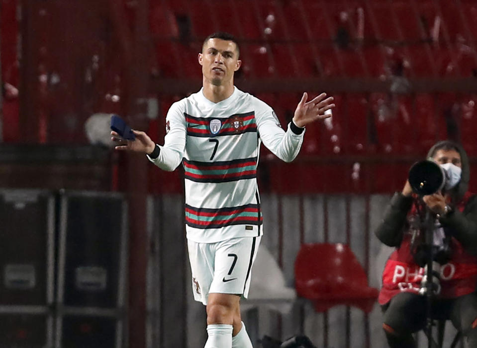 Portugal's Cristiano Ronaldo holding captain's armband, left, reacts during the World Cup 2022 group A qualifying soccer match against Serbia at the Rajko Mitic stadium in Belgrade, Serbia, Saturday, March 27, 2021. The captain's armband which Cristiano Ronaldo threw to the pitch after his overtime winning goal was disallowed in a World Cup qualifier against Serbia has been put on auction Tuesday March 30, 2021. The armband is being auctioned by a charity group raising money for surgery of a six-month-old boy from Serbia suffering spinal muscular atrophy. (AP Photo/Darko Vojinovic)