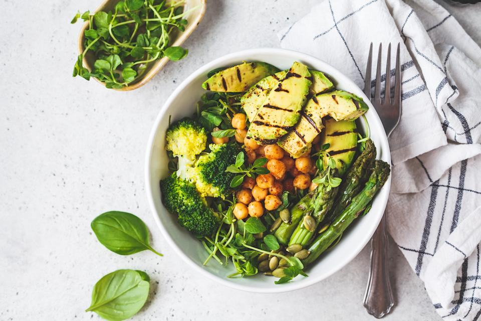 Buddha bowl with grilled avocado, asparagus, chickpeas, pea sprouts and broccoli. Vegan food concept.