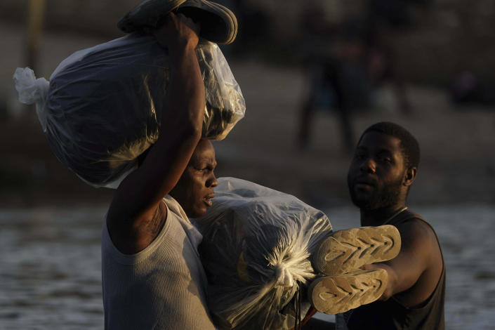 FILE - In the Sept. 22, 2021, file photo, migrants, many from Haiti, wade across the Rio Grande from Del Rio, Texas with their belongings to return to Ciudad Acuna, Mexico to avoid possible deportation from the U.S. The Border Patrol's treatment of Haitian migrants, they say, is just the latest in a long history of discriminatory U.S. policies and of indignities faced by Black people, sparking new anger among Haitian Americans, Black immigrant advocates and civil rights leaders.(AP Photo/Fernando Llano, File)