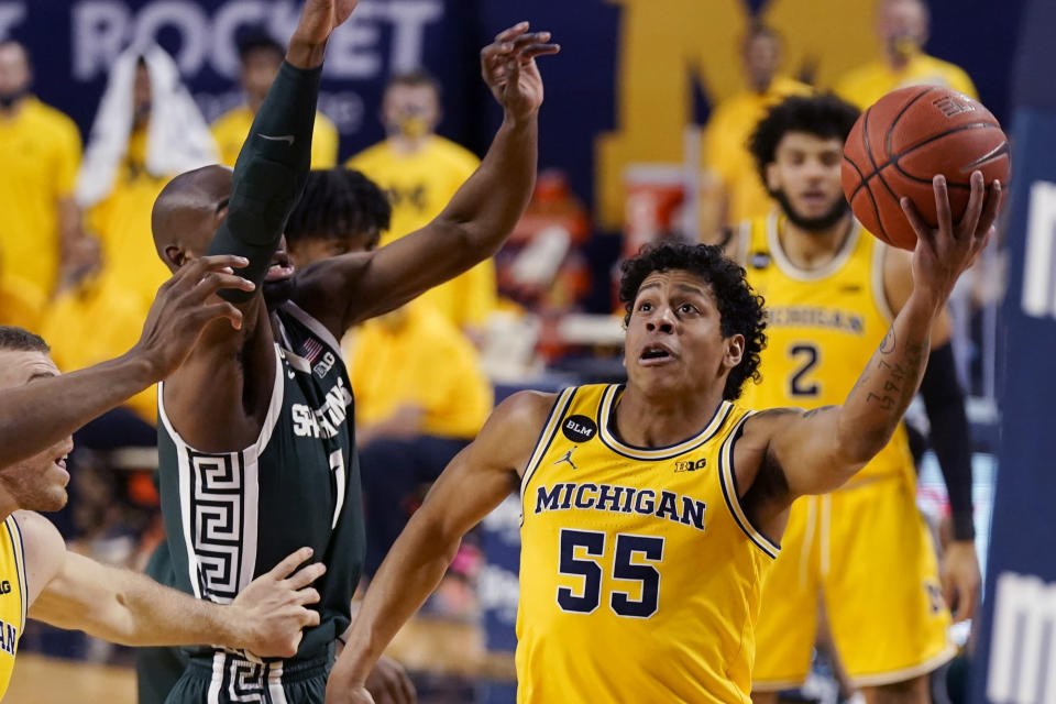 Michigan guard Eli Brooks (55) makes a layup as Michigan State guard Joshua Langford (1) defends during the first half of an NCAA college basketball game, Thursday, March 4, 2021, in Ann Arbor, Mich. (AP Photo/Carlos Osorio)