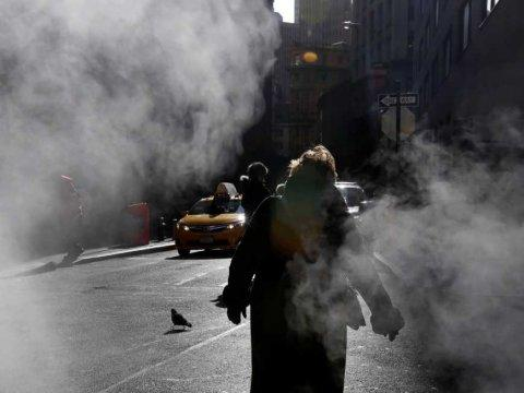 woman in financial district walking steam clouds