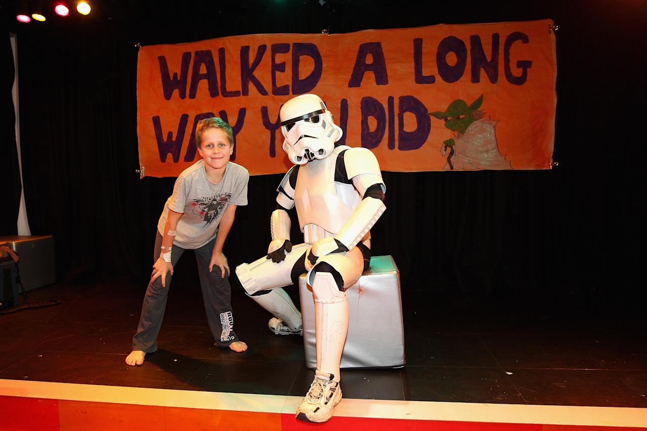 Jacob French poses with a patient after completing his trek at the Sydney Children's Hostpital on April 4, 2012 in Sydney, Australia. French today completed the over 5,000 km trek from Perth to Sydney on foot, donning a full body stormtrooper costume he successfully raised over $100,000 for the Starlight Children's Foundation. Since July 2011, Jacob has walked 10 hours a day, Monday to Friday, lost over 12kg in weight, and gone through seven pairs of shoes. The Starlight Children's Foundation provides programs to help lift the spirits of sick children in hospitals accross Australia.  (Photo by Cameron Spencer/Getty Images)