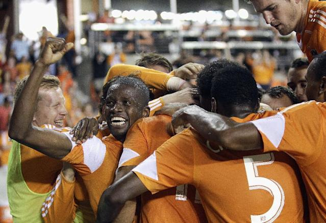 Houston Dynamo midfielder Boniek Garcia, facing camera, celebrates with teammates after forward Will Bruin scored his second goal of the game in the second half against the Montreal Impact during a knockout-round match in the MLS Cup soccer playoffs, Thursday, Oct. 31, 2013, in Houston. Houston won 3-0. (AP Photo/Bob Levey)