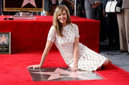 Actress Allison Janney poses on her star after it was unveiled on the Hollywood Walk of Fame in Los Angeles