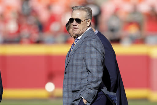 FILE - In this Sunday, Oct. 28, 2018, file photo, John Elway, general manager and president of football operations of the Denver Broncos, follows warm ups before an NFL football game against the Kansas City Chiefs in Kansas City, Mo. The Broncos play the San Francisco 49ers Sunday in the latest chapter of the friendly feud between the two superstars-turned-GMs whose paths have crossed throughout their careers, both on the football field and the front office. (AP Photo/Orlin Wagner)