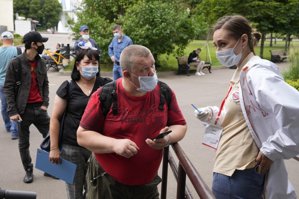 A man speaks to a medical worker as pother people wearing face masks to protect against coronavirus stand in line to get a coronavirus vaccine at a vaccination point in Gorky Park in Moscow, Russia, Wednesday, June 30, 2021. Russia was among the first in the world to announce and deploy a coronavirus vaccine last year, but so far only about 23 million, just over 15% of the population have received at least one vaccine shot. Hampered by widespread vaccine hesitancy and limited production capacity, Russia's vaccination rates have picked up in recent weeks, after authorities in many regions made shots mandatory for employees in certain sectors. (AP Photo/Alexander Zemlianichenko)