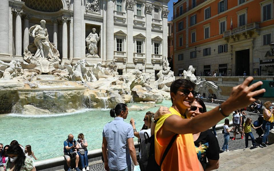 A couple takes a selfie photo as people gather by the Trevi fountain - AFP