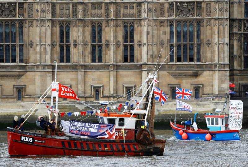 FILE PHOTO: Part of a flotilla of fishing vessels campaigning to leave the European Union sails past Parliament on the river Thames in London