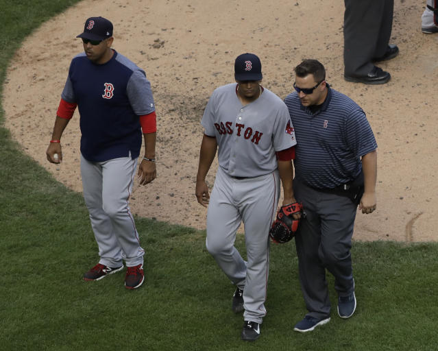 Boston Red Sox relief pitcher William Cuevas, center, leaves with a team trainer and manager Alex Cora, left, after an injury in the sixth inning of a baseball game against the Chicago White Sox, Sunday, Sept. 2, 2018, in Chicago. (AP Photo/Nam Y. Huh)