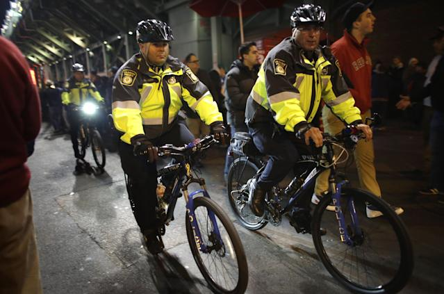 Boston Transit Police patrol a street on bicycles outside Fenway Park before Game 6 of baseball's World Series between the Boston Red Sox and St. Louis Cardinals Wednesday, Oct. 30, 2013, in Boston. (AP Photo/Steven Senne)