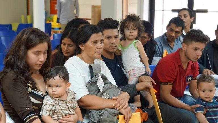 Migrants wait to be assisted by volunteers in a Humanitarian Respite Center in the border town of McAllen, Texas