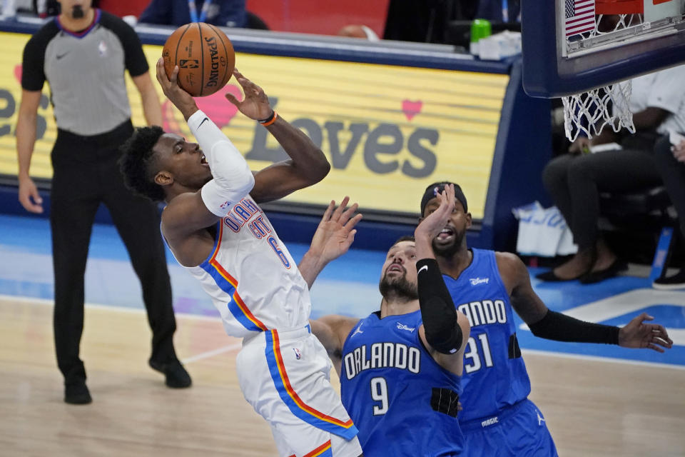 Oklahoma City Thunder guard Hamidou Diallo (6) shoots in front of Orlando Magic center Nikola Vucevic (9) and guard Terrence Ross (31) during the second half of an NBA basketball game Tuesday, Dec. 29, 2020, in Oklahoma City. (AP Photo/Sue Ogrocki)