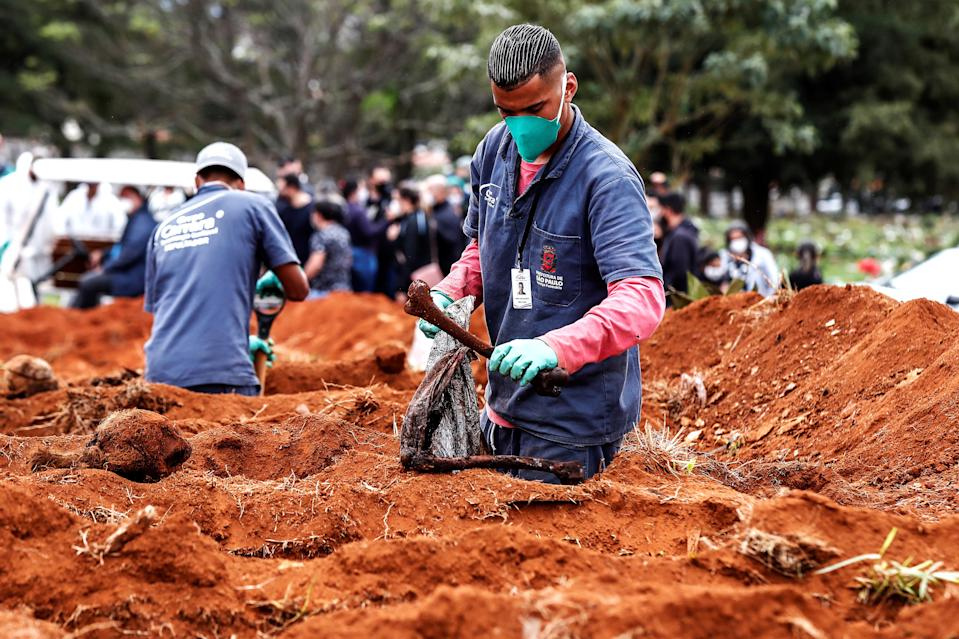Gravediggers of the Vila Formosa cemetery, the largest in Latin America, exhume old graves to open new spaces for those deceased by Covid-19, in Sao Paulo, Brazil.