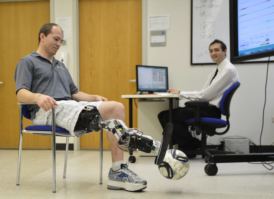 """In this Oct. 25, 2012 photo, Zac Vawter kicks a soccer ball with an experimental """"bionic"""" leg as biomedical student Aaron Young makes adjustments to the leg at the Rehabilitation Institute of Chicago. After losing his right leg in a motorcycle accident, the 31-year-old software engineer signed up to become a research subject, helping test a trailblazing prosthetic leg that's controlled by his thoughts. He will put this leg to the ultimate test Sunday, Nov. 4 when he attempts to climb 103 flights of stairs to the top of Chicago's Willis Tower, one of the world's tallest skyscrapers. (AP Photo/Brian Kersey)"""