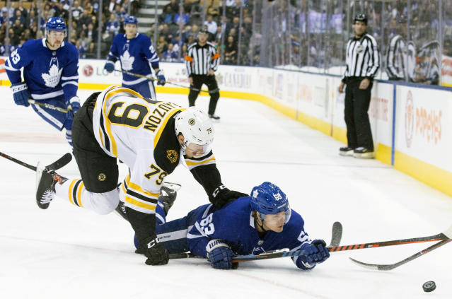 Toronto Maple Leafs' Tyler Ennis (63) battles for the puck with Boston Bruins Jeremy Lauzon during first-period NHL hockey game action in Toronto, Monday, Nov. 26, 2018. (Chris Young/The Canadian Press via AP)