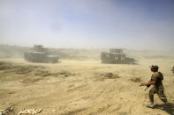 FILE - In this June 15, 2016, file photo, Iraqi security forces advance their positions during the fight against Islamic State militants in Fallujah, Iraq. The U.S. launched its invasion of Iraq on March 20, 2003, unleashing a war that led to an insurgency, sectarian violence and tens of thousands of deaths. (AP Photo/Anmar Khalil, File)