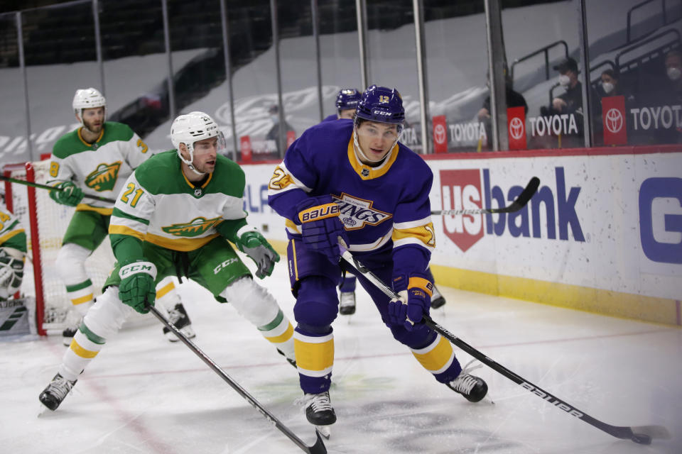 Los Angeles Kings center Trevor Moore (12) skates with the puck in front of Minnesota Wild defenseman Carson Soucy (21) in the first period during an NHL hockey game, Saturday, Feb. 27, 2021, in St. Paul, Minn. (AP Photo/Andy Clayton-King)