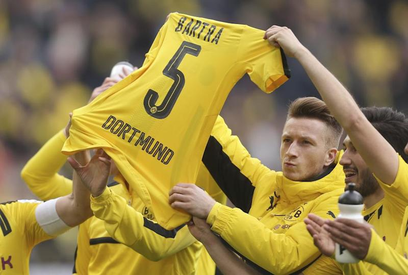 Dortmund players hold up the No 5 shirt of teammate Marc Bartra after a match between Borussia Dortmund and Eintracht Frankfurt on Saturday. Bartra was seriously injured in the bomb attack on Dortmund's bus on 11 April.