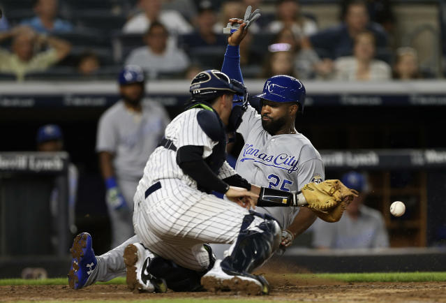 Kansas City Royals' Brian Goodwin (25) scores before New York Yankees catcher Kyle Higashioka, left, gets the ball on a single by Rosell Herrera in the sixth inning during the second baseball game of a doubleheader Saturday, July 28, 2018, at Yankee Stadium in New York. (AP Photo/Rich Schultz)