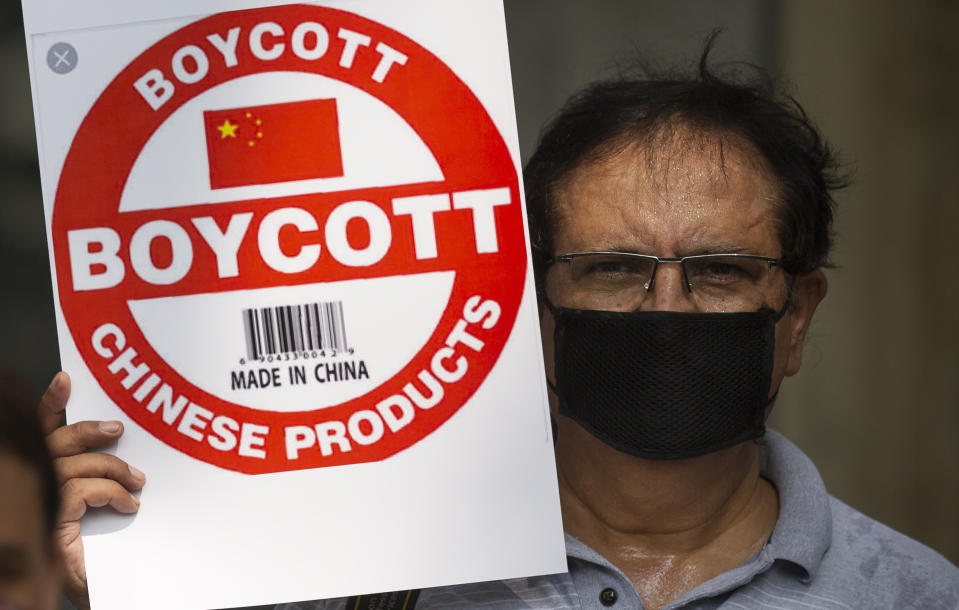 An Indian journalist holds a placard calling for boycott of Chinese products during a protest organized by Working Journalists of India, in New Delhi, India, Tuesday, June 30, 2020. India on Monday banned 59 apps with Chinese links, saying their activities endanger the country's sovereignty, defense and security. India's decision comes as its troops are involved in a tense standoff with Chinese soldiers in eastern Ladakh in the Himalayas that started last month. India lost 20 soldiers in a June 15 clash. (AP Photo/Altaf Qadri)